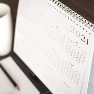 Desktop calendar sitting on desk showing year of 2021